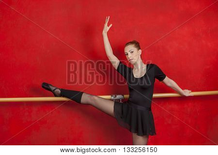Confident Ballerina Practicing At Barre Against Wall