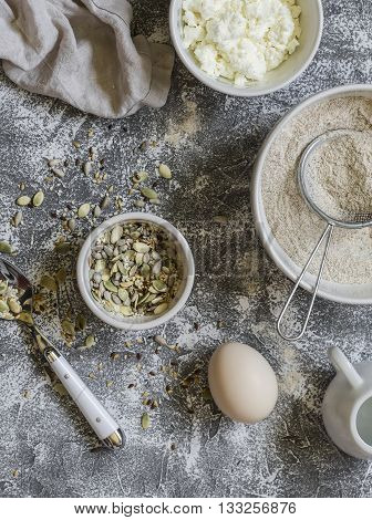 Ingredients for cooking whole grain multi seed bread - whole wheat flour eggs ricotta cheese seeds on a grey stone background. Baking background