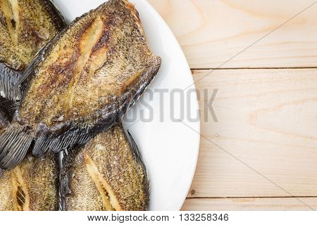 Fried Trichogaster pectoralis cut in stripes before fry for crisp, 'Sa-lid' fish thai food in plate on wooden table.