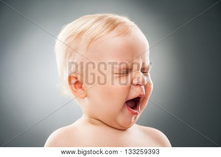 Funny baby squinting eyes and opening mouth.Studio shot