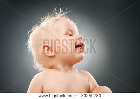 Portrait of lovely blonde baby with messy hair and open mouth looking away