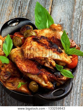 Delicious Roasted Chicken Thighs with Green Olives Cherry Tomatoes and Basil in Black Fry Pan closeup on Rustic Wooden background