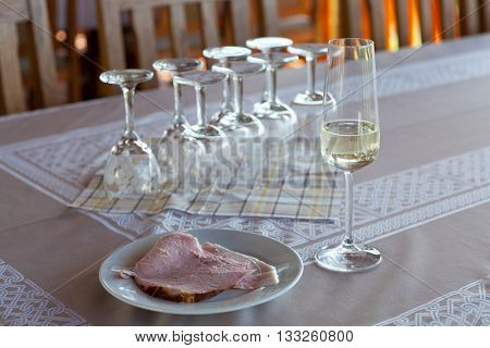 Champagne glass and a cooked ham on a plate