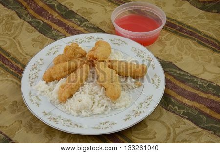 Sweet and sour chicken on rice with container of sweet and sour sauce in container