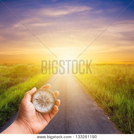Hand Man Holding Compass Navigator On Road Way With Sunlight.