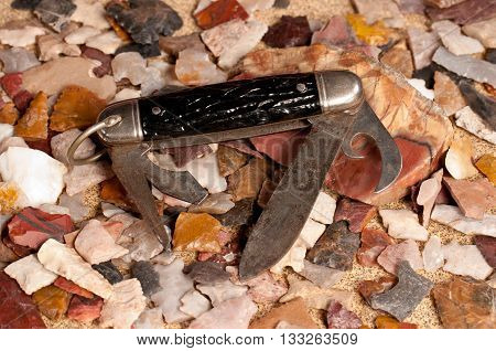 A still life photo of a rusty old pocket knife with indian arrowhead chips on top of sandpaper