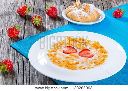 healthy corn flakes with milk and strawberries in a white dish bun with cheese on a saucer on an old rustic table studio lights close-up view from above