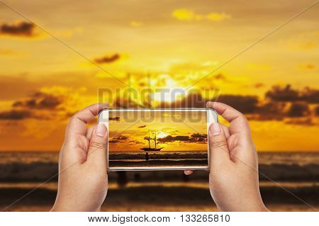Hand with smart phone shooting photograph on blurred beach sunset and transport boat in twilight