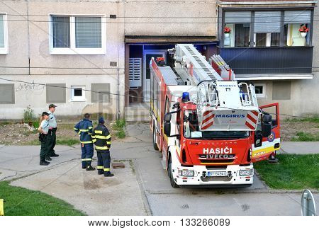 Bytca, Slovakia - June 4, 2016: Firefighters at beginning of action stand with two police officers next to the fire truck