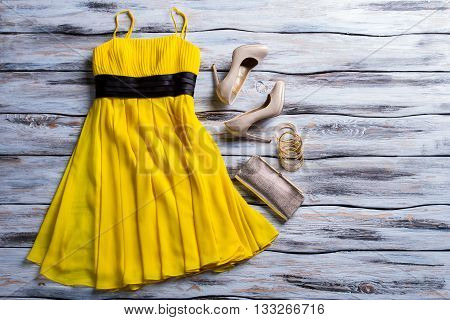 Yellow dress, purse and shoes. Casual yellow dress with accessories. Lady's charming summer outfit. New clothes and heel shoes.