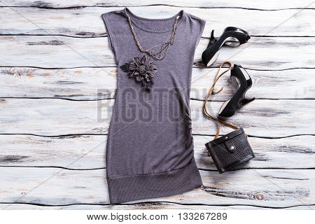 Gray evening top and necklace. Flower applique top with bag. Designer clothes and classy footwear. Dark evening outfit on display.