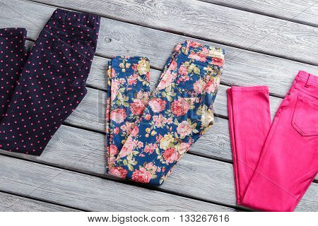 Folded casual trousers with print. Navy, blue and pink pants. Fashionable pattern and quality fabric. Best merchandise on display.