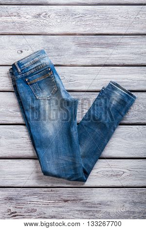 Simple jeans of blue color. Jeans on gray wooden background. Best merchandise in jeans store. Quality fabric and plain design.