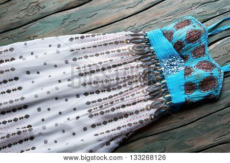 Blue and white summer dress. Long casual dress with print. Sleeveless garment of light fabric. Dress lying on workshop table.