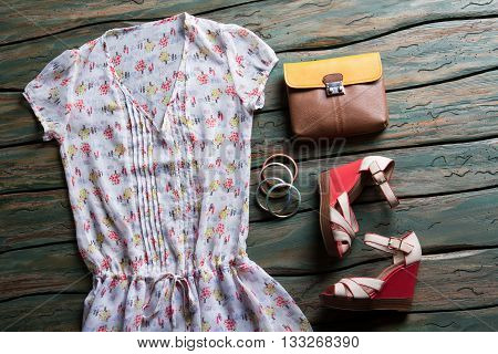 Summer blouse and bicolor bag. Colorful bracelet set and shoes. Clothes on green wooden table. Brand new footwear on display.