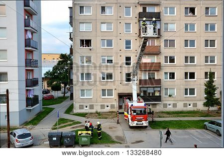 Bytca, Slovakia - June 4, 2016: Firefighters in action two men uprise in telescopic boom basket of fire truck. Some people are watching block of flats in background.