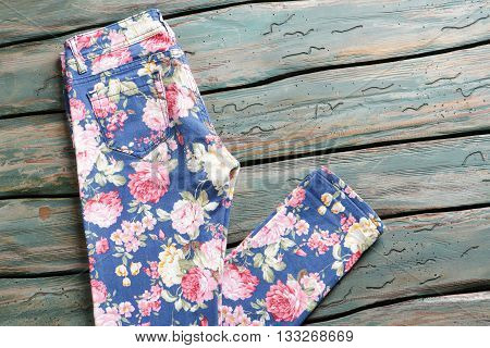 Folded pants with flower print. Casual floral trousers. Clothing item on green table. Designer clothing on auction.