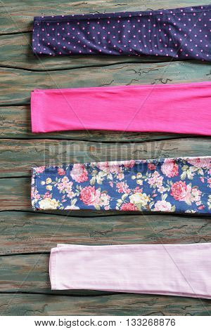 Pieces of cloth with prints. Fabric on green wooden background. New materials in clothing workshop. Clothes repair at low price.