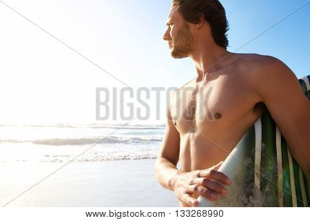 Male Surfer Carrying Surfboard At The Beach