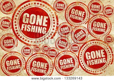 gone fishing, red stamp on a grunge paper texture