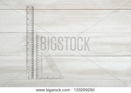 Plastic triangular ruler and straight-edge ruler on wooden table. Mathematics. Science. Calculation and drawing.