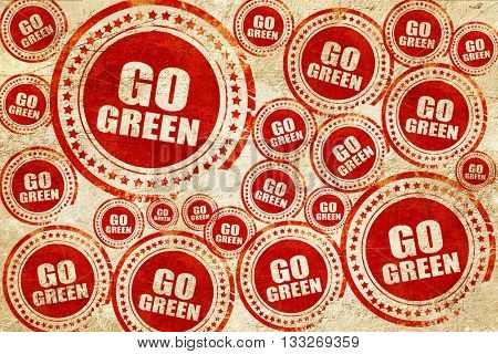 go green, red stamp on a grunge paper texture