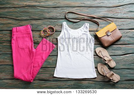 Pink pants and tank top. Trousers with sandals and purse. Lady's clothing from brand store. Trendy summer look.