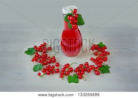 Red currant liqueur in the little glass and bottle with berries on the white wooden background