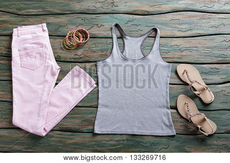 Gray tank top and pants. Light pink trousers and footwear. Summer outfit with simple top. Discounted goods in brand store.