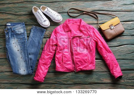 Pink jacket and blue jeans. Denim pants and white footwear. Canvas shoes on green shelf. Female outerwear for spring.