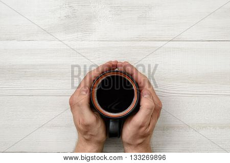 Close-up hands of man holding a cup of coffee. Top view. Workplace of office man. Coffee house. Uplifting mood. Coffee break. Relax. Willingness to work overtime. Conducive working environment. Increasing productivity in the mornings. Improving mood and p