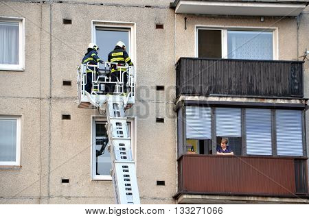 Bytca, Slovakia - June 4, 2016: Two firefighters into telescopic boom basket of fire truck try to get to the flat balcony. Old woman is watching them from next balcony.