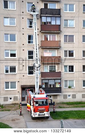 Bytca, Slovakia - June 4, 2016: Firefighters in action a man uprise in telescopic boom basket of fire truck. Block of flats in background.