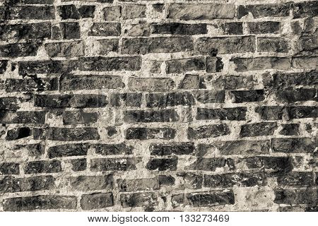 texture of the old destroyed brick wall for a rough vintage background or for ancient wallpaper of monochrome tone
