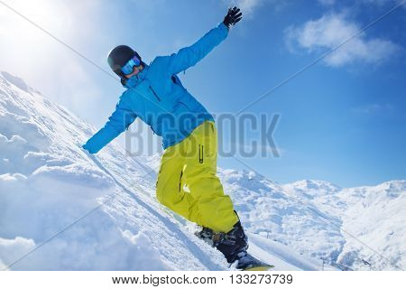 Snowboarder in helmet and goggles riding a slope