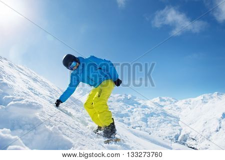 Active man in snowboard outfit in the snowy mountains