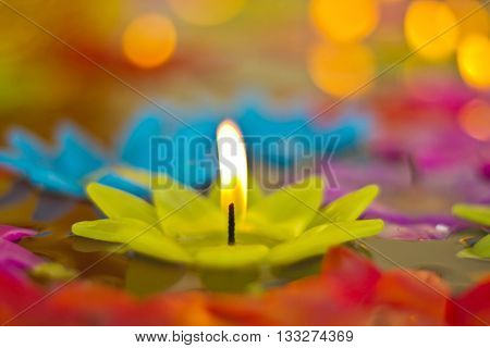 One light candle burning brightly in background, blurred