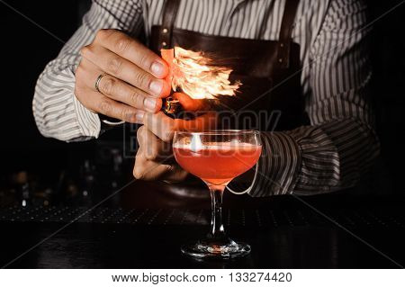 The bartender makes flame fire fromorange zest above cocktail