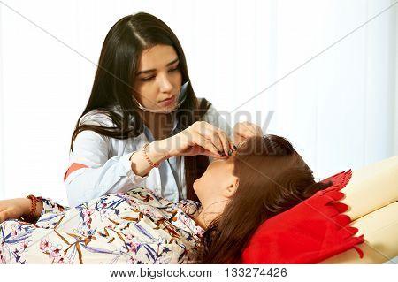 Master makes threading eyebrow correction procedure in salon