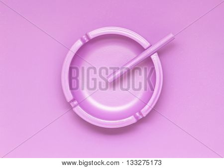 Creative concept photo of a painted pink ashtray with a cigarette on pink background.