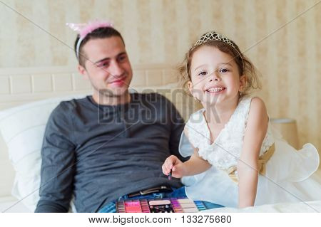 Cute little girl in princess dress putting on colorful make up on her father