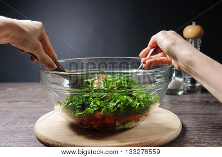 Cooking salad. Young woman cooking vegetable salad at home. Hands stirs vegetarian salad with fresh tomatoes, cucumber on wood table against dark background on rustic kitchen.