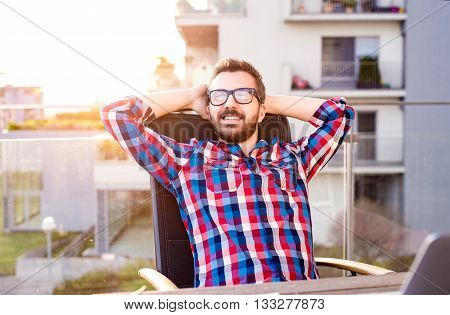 Young hipster businessman in checked shirt sitting on a balcony, relaxing