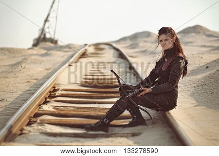 Tribal girl in leather costume with a crossbow on the rails in the desert