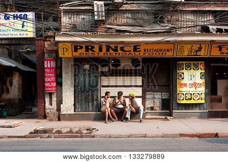 KOLKATA, INDIA - JAN 20, 2013: Poor people chating at front of indian cuisine restaurant on January 20, 2013. Third biggest indian city Calcutta with its suburbs is home to approximately 14.1 mill.people