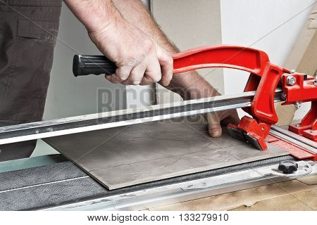 Home improvement, - close-up of handyman laying tile