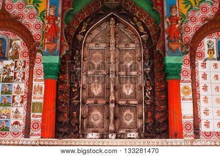 UTTAR PRADESH, INDIA - JAN 27, 2013: Beautiful metal doors of the Hanuman temple framed by colorful figures patterns and drawings on January 27, 2013 in India. Uttar Pradesh state covers 243290 km2