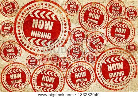 Now hiring sign, red stamp on a grunge paper texture