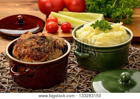 Meat cutlets and mashed potatoes in ceramic pots.