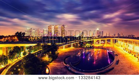Singapore travel tourism concept - vintage retro effect filtered hipster style image of  panorama of Singapore skyline illumintaed in the evening twilight